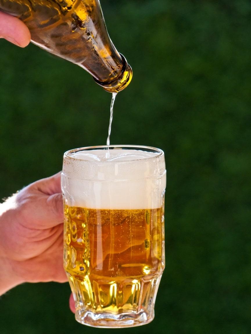 Frisches Bier aus einer Bierflasche wird in Bierglas ...