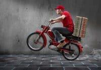 Mann auf einem Zweirad liefert Pizzen aus