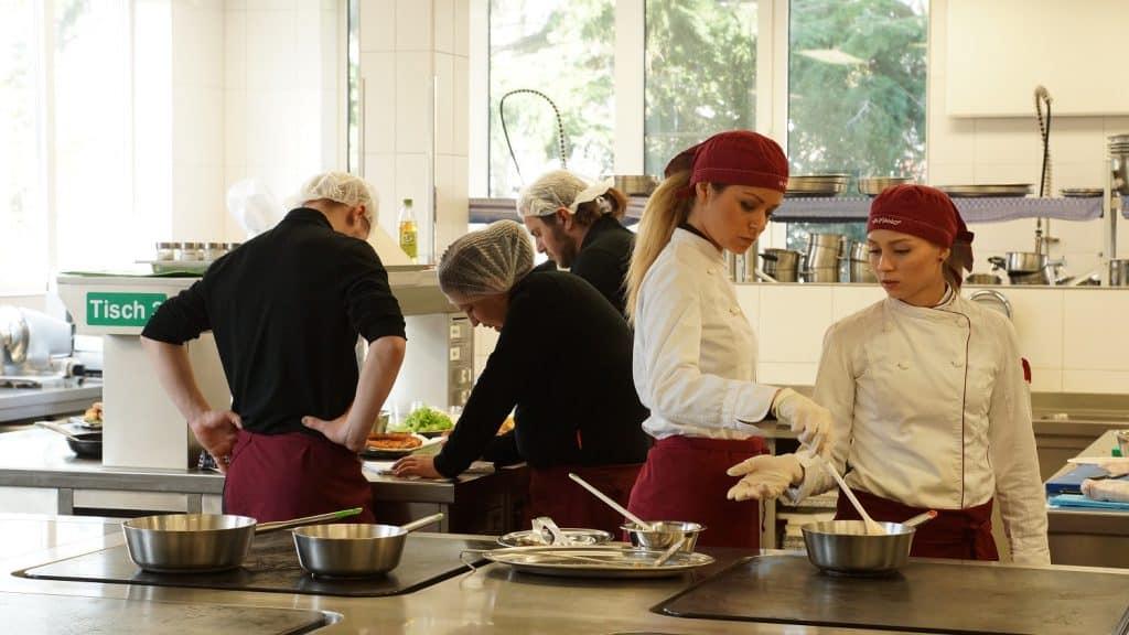 Junge Männer und Frauen als Auszubildende in der Gastronomie bei der Arbeit.