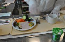 Ein Tablett wird auf dem Laufband mit Speisen bestückt.