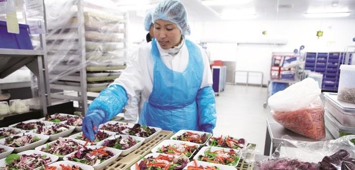 Eine Catering-Mitarbeiterin vor Essenstabletts