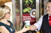 Eine DB-Servicekraft überreicht einer Reisenden einen Fairtrade-Kaffee