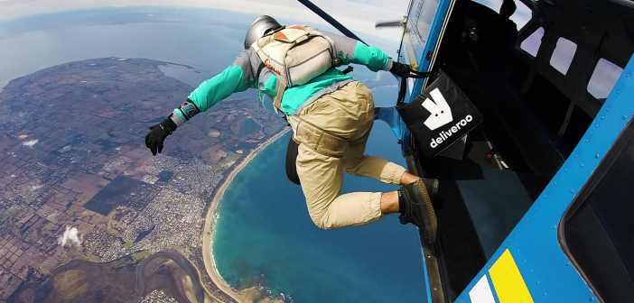 Ein Delibveroo-Mitarbeiter springt mit einem Rucksack aus einem Hubschrauber.