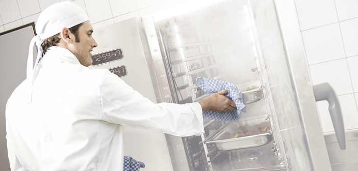 Ein Koch schiebt ein GN-Behälter in einen Kombidämpfer