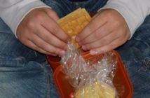 Kind isst aus geöffneter Lunchbox.