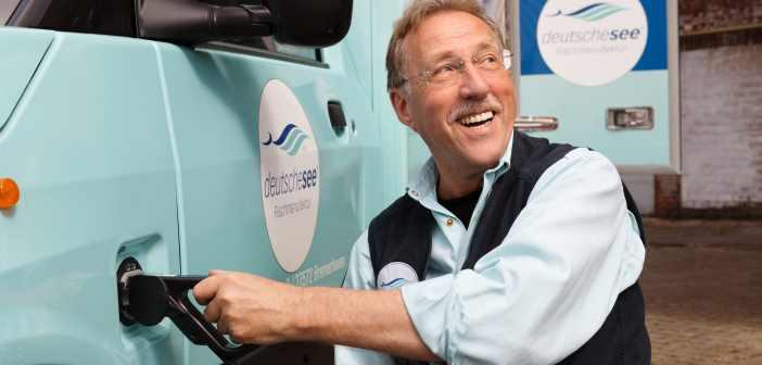Ein Deutsche-See-Mitarbeiter lädt den neuen E-Lieferwagen mit Strom auf.